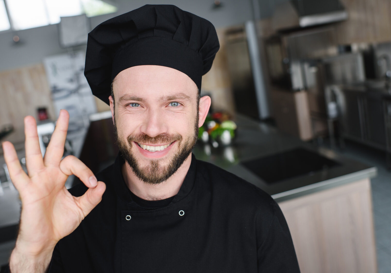 smiling handsome chef showing okay gesture at restaurant kitchen