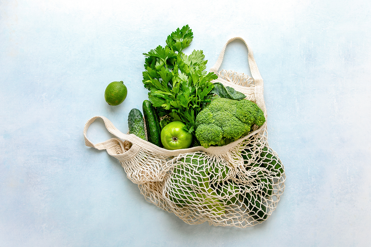 View from above on eco friendly bag filled with green organic vegetables, zero waste informed consumption concept
